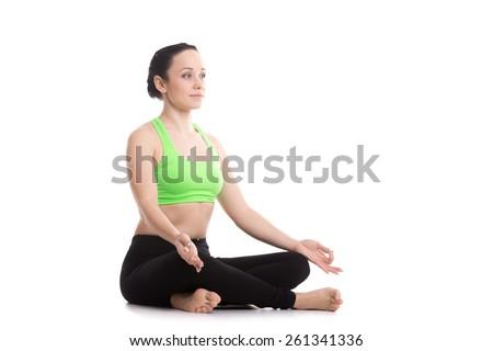 Serene girl practicing yoga, Sitting in Easy (Decent, Pleasant Pose), Sukhasana, asana for meditation, pranayama, breathing, copy space - stock photo