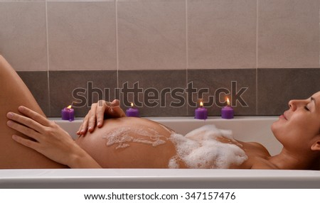 Serene pregnant woman in relaxing candle ambient at bathtub before give Birth. Beautiful young pregnant woman at beauty salon spa getting a body treatment. - stock photo