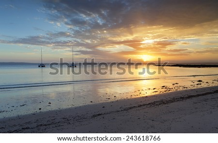 Serene sunset with catamarans on the  tranquil waterw at Cabbage Tree beach, Jervis Bay - stock photo