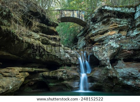 Serene Waterfall. Waterfall with a stone bridge crossing over the top. Hocking Hills State Park. Logan, Ohio. - stock photo