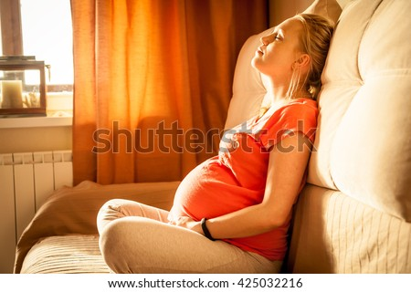 Serene woman during pregnancy relaxing at home with closed eyes. Sunlight is falling from window on woman face. - stock photo