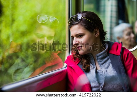 Serene woman sitting inside a train wagon, looking out the window, her reflection next to her.