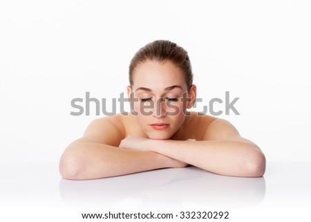 serene young female model with eyes closed after a massage,with folded arms on white glass for fresh relaxing pampering,studio shot,white background - stock photo