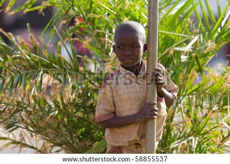 SERENGETI, TANZANIA - JUNE 6: Unidentified African Kid looking behind a bar on June 6, 2010 in the Serengeti, Tanzania. - stock photo