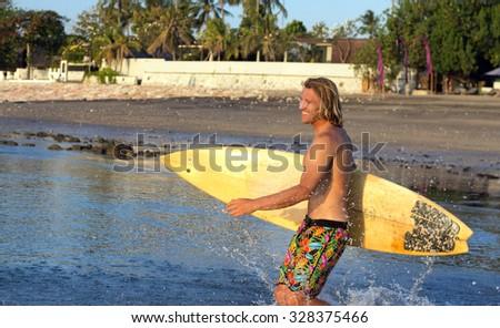 Serfer man with serf. Bali, Indonesia. - stock photo