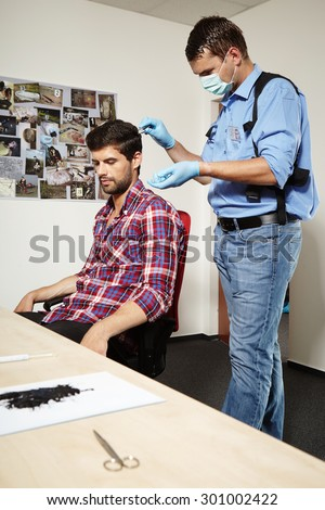Serial criminal catched by police and giving sample of hair - stock photo