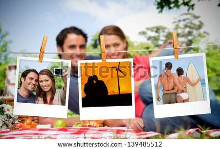 Serial instant photos of holiday scenes hung with a peg on a laundry line with couple having a picnic on the background - stock photo