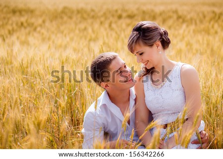 series. a love story. happy bride and groom in a yellow field of wheat. close-up - stock photo