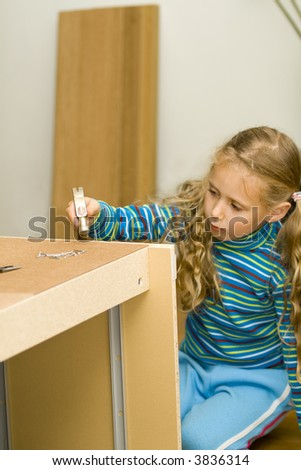 Series - girl helping to assemble a new furniture.