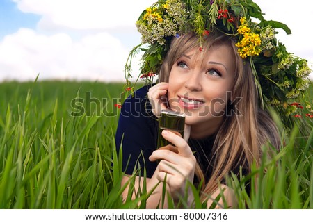 series of closeup portrait of a beautiful girl in a field with a wreath talking on the phone - stock photo