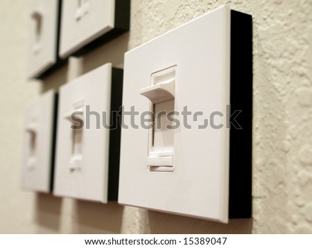 Series of Dimmer Switches on wall perspective - stock photo
