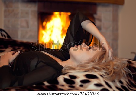 series of the beautiful girl lies at a burning fireplace for new year - stock photo