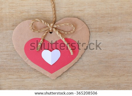 Series of Valentines Card, Heart Shape Blank Cardboard with Flax Cord hanging over wood background. - stock photo
