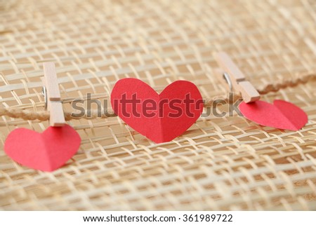 Series of Valentines Card. Three Red heart paper cut with clothes pin on wooden weaving background, in very shallow focus. Image of Valentines day. - stock photo