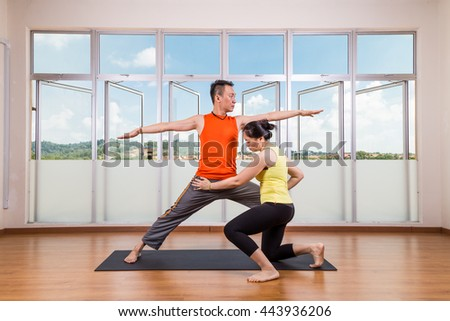 Series of yoga instructor correcting student performing Warrior 2 or Virabhadrasana 2 in studio