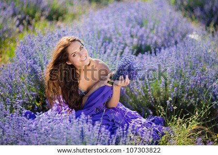 Series. Portrait of beautiful romantic woman in fairy field of lavender with bouquet - stock photo