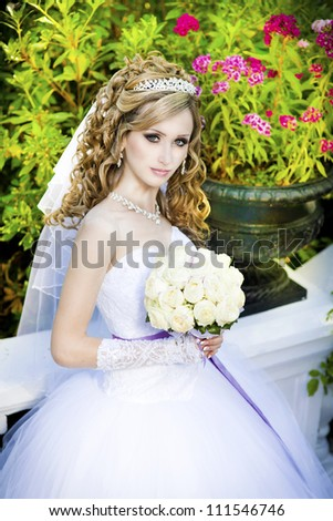 Series. Portrait of the young beautiful bride. beautiful slim woman in luxurious wedding dress with bridal flowers outdoor - stock photo