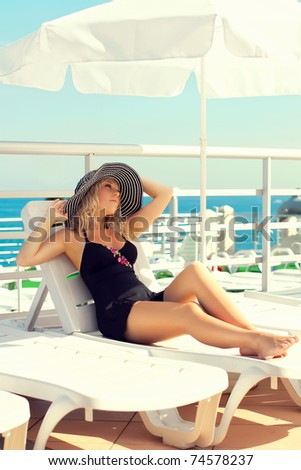 Series The lady in a hat sunbathes on the yacht in the sea - stock photo