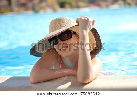 Series the smart blonde in a hat in pool of expensive hotel - stock photo