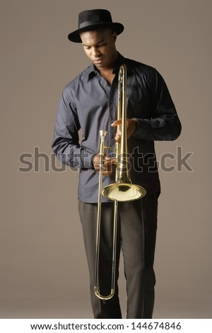 Serious African American man with trombone standing against brown background - stock photo
