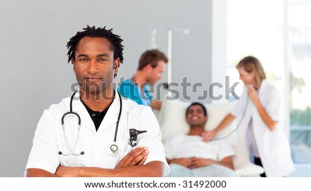 Serious African doctor with folded arms and patient in the background