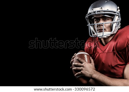 Serious American football player looking away while holding ball against black