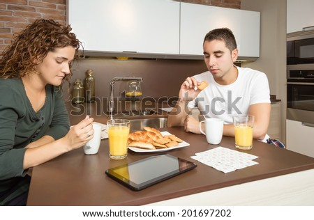 Serious and bored young couple having a breakfast in the home kitchen - stock photo