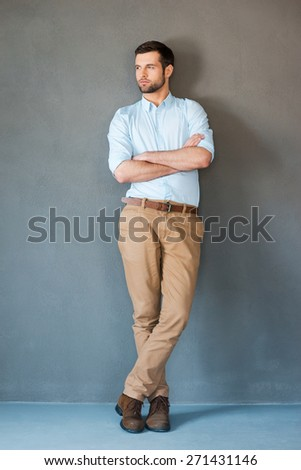Serious and confident. Full length of handsome young man in shirt keeping arms crossed and looking away while standing against grey background