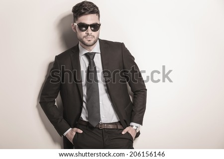 serious and cool sexy business man wearing sunglasses and standing with hands in his pockets - stock photo