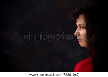 Serious and somber looking woman against a dark background. Copy space on left. - stock photo