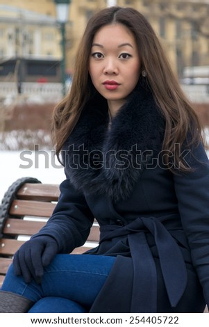 serious Asian girl in blue coat looks right - stock photo