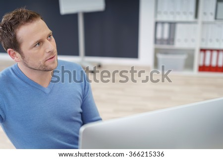 Serious attentive informal young businessman sitting behind his computer looking up to the side as he listens to a colleague, with copy space - stock photo