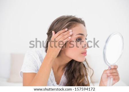 Serious attractive brunette looking at mirror in bright bedroom - stock photo