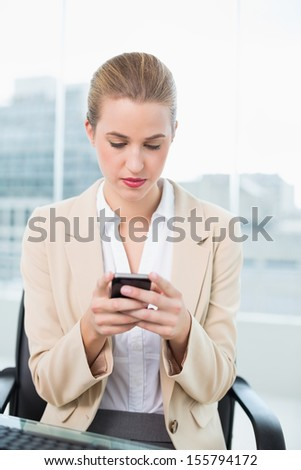 Serious attractive businesswoman in bright office text messaging - stock photo
