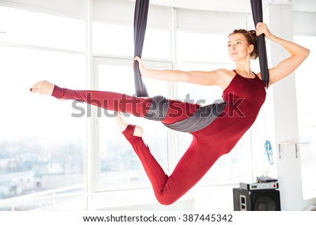 Serious attractive young woman doing antigravity yoga using hammock in studio - stock photo
