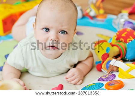 serious baby is laying on the carpet - stock photo