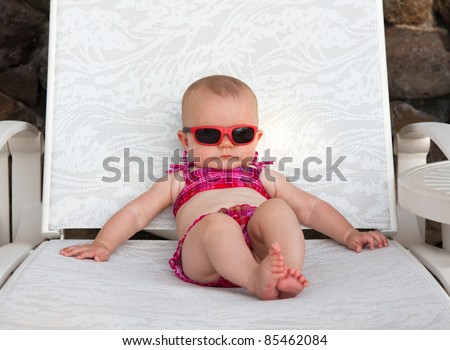 Serious baby on beach in bikini - stock photo