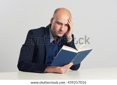 serious bald man sitting and reading a book - stock photo