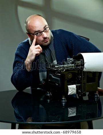 Serious bald writer in glasses. Sitting at a typewriter - stock photo