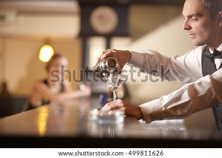 Serious bartender preparing cocktail in empty bar