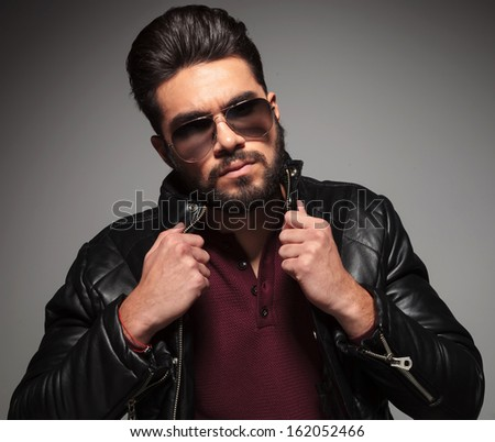 serious bearded fashion man is pulling his jacket's collar and looks at the camera