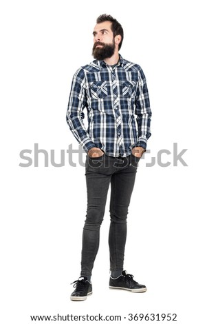 Serious bearded hipster in checked plaid shirt with hands in pockets looking away. Full body length portrait isolated over white studio background.