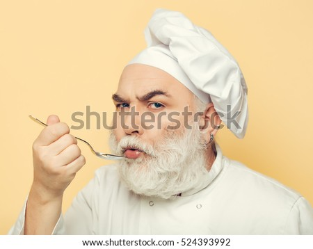Serious bearded man cook in hat tasting food with spoon in studio on yellow background