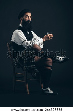 Serious Bearded Man Wearing Fashionable Attire Sitting on a Chair and Crossing Legs While Holding a Glass of Wine While Looking at the Camera. Captured in Studio on Black Background. - stock photo