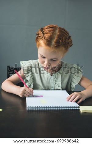 serious beautiful little girl drawing in album