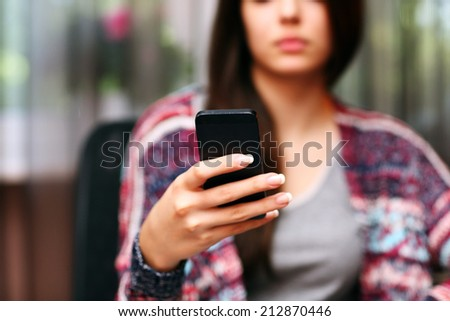 Serious beautiful woman using smartphone at home. Focus on smartphone - stock photo