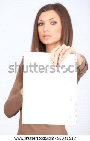 serious beautiful young woman in brown blouse with blank card - stock photo