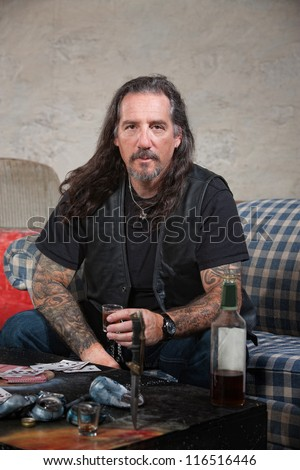 Serious biker gang member with liquor and dagger on table