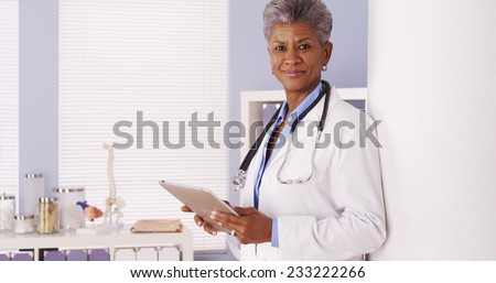 Serious Black Senior doctor working on tablet in office - stock photo