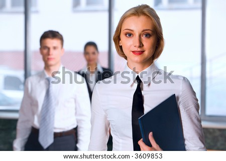 Serious blond Caucasian businesswoman holding blue paper case looking at camera and two walking businesspeople on the background